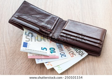 Open wallet with euro banknotes on the wooden table - stock photo