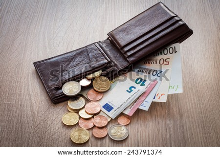 Open wallet with euro currency on the wooden table - stock photo