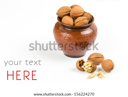 open walnuts closeup in brown pot on white background - stock photo