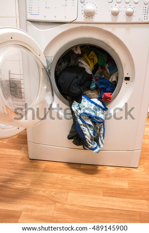 Open Washing Machine with Dirty Clothes on the Floor.