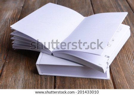 Open white book on wooden table, close-up - stock photo