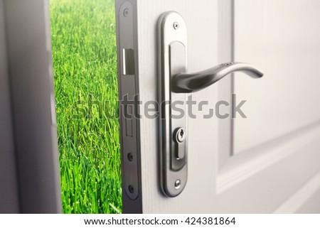 Open white door to green field - stock photo