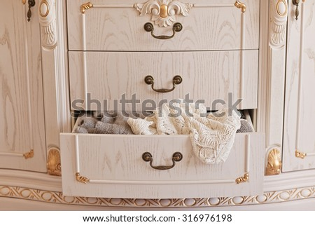 Open white vintage wardrobe. Wool sweaters in closet. Winter mood - stock photo