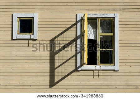 Open window in sunshine casting shadow on wall of old yellow wooden house - stock photo