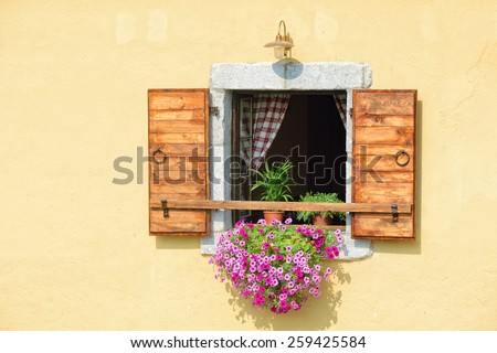 Open window with wooden shutters and blooming flowers in pots. Montenegro - stock photo
