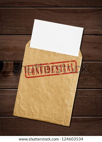 Open yellow envelope with top secret stamp and papers, on wooden table, clipping path. - stock photo