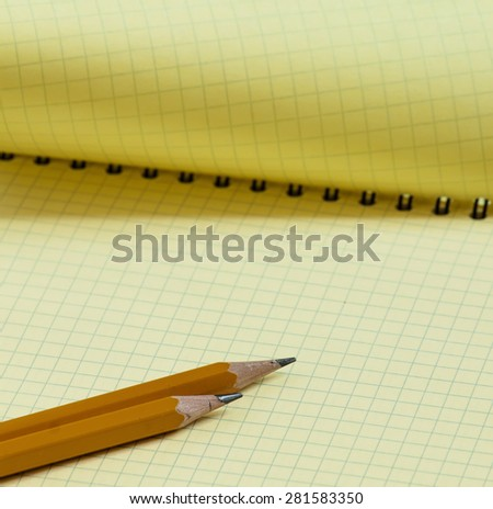 Open yellow notebook with a pencil, selective focus - stock photo