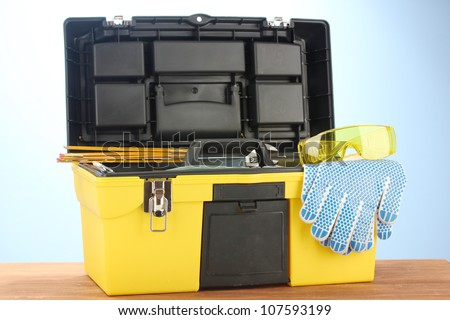 Open yellow tool box with tools  on blue background close-up