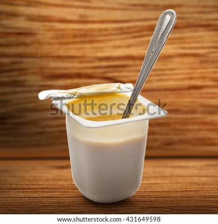 Open yogurt in pot with metal spoon closeup