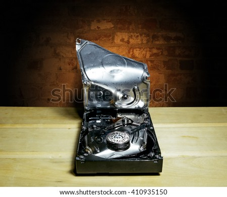 Opened and broken the hard drive from the computer against a brick wall - stock photo