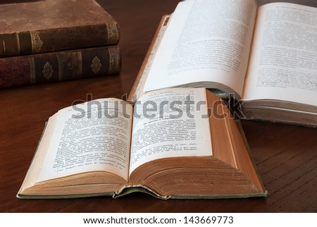 Opened and closed Rustic antique books on a wooden table