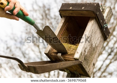 opened birdhouse with old nest in it, man try to remove it with a shovel - stock photo