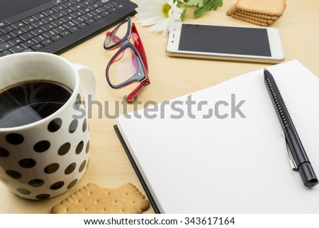 Opened blank notebook with pen, keyboard  and cup of coffee and cookies, on wooden desktop. - stock photo