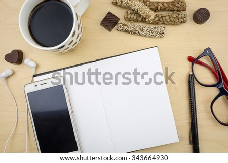 Opened blank notebook with smartphone, pen and cup of coffee, on wooden desktop. - stock photo