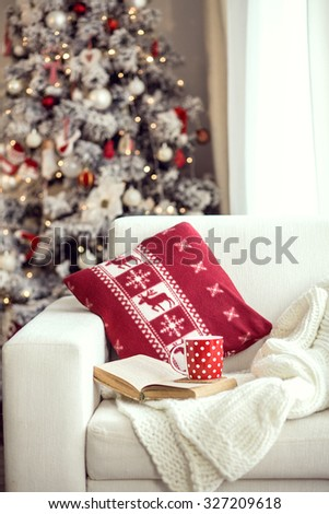 Opened book and a cup of tee on the cozy armchair with warm blanket and cushion on it near Christmas tree. Text in the book is not recognizable.  - stock photo