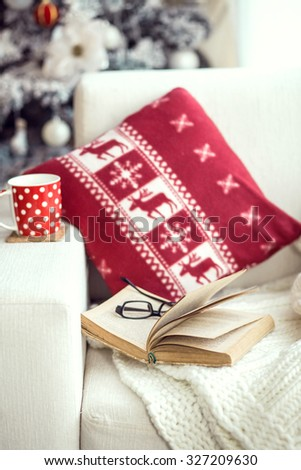 Opened book and a cup of tee on the cozy chair with warm blanket and cushion on it near Christmas tree. Text in the book is not recognizable.  - stock photo