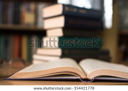 Opened Book and a Stalk of Books on the Background