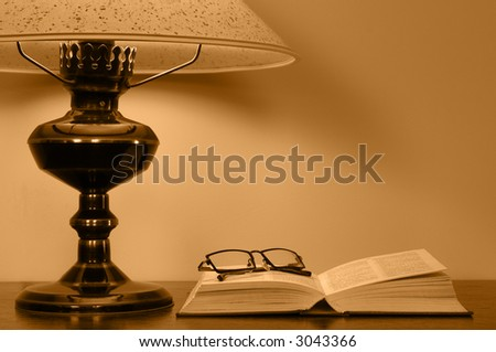 Opened book and glasses lying close by bedside lamp.