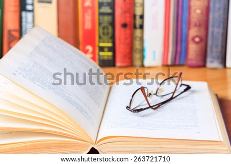 Opened book and glasses on the desk in the library - stock photo