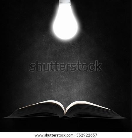 Opened book and glowing light bulb above pages