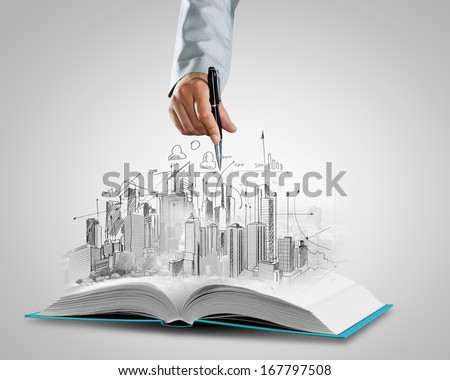 Opened book and hand drawing building sketches - stock photo