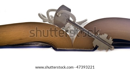 Opened book and key. Isolated - stock photo
