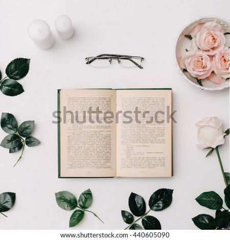 Opened book, glasses, pink roses on white background. Flat Lay - stock photo