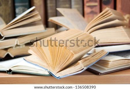 Opened book lying on the bookshelf - stock photo