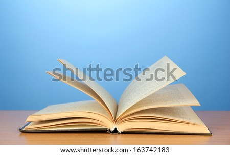 Opened book on color background