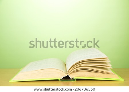 Opened book on color background - stock photo