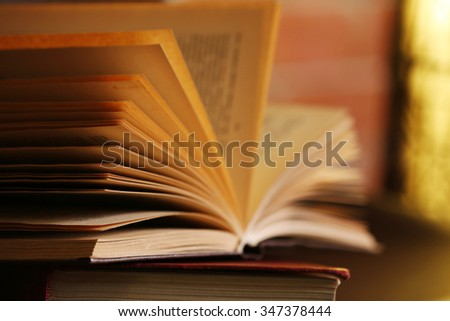 Opened book on modern chair, close up, blurred background - stock photo