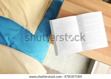 Opened book on wooden bedside table near crumpled bed