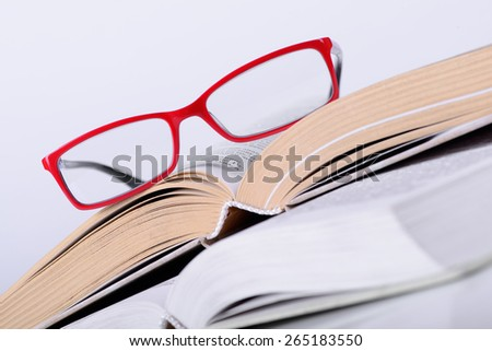 opened book with a glasses on it close-up - stock photo
