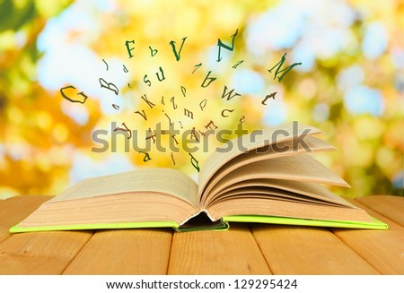 Opened book with letters flying out of it  on bright background - stock photo