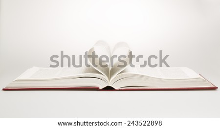Opened book with sheets in the form of heart, studio shot - stock photo