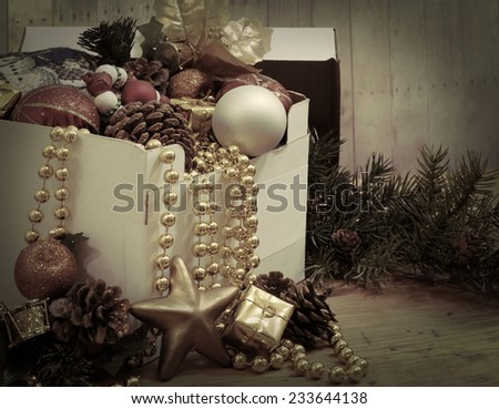 Opened box with a variety of Christmas decorations spilling out with vintage, instagram style filter applied.  Decorations include Christmas balls, beads, pine-cones, silk décor and a gold star - stock photo