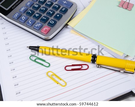 Opened business diary, pen and calculator