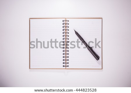 opened cap calligraphic pen on lined recycled paper notebook on white desktop with vignette effect - stock photo