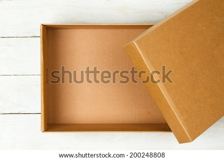 Opened cardboard box on a wooden table - stock photo