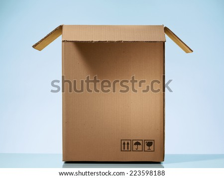 Opened cardboard box on beautiful light blue background - stock photo