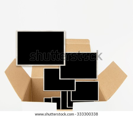 Opened carton box with old photograph templates, isolated on white. - stock photo