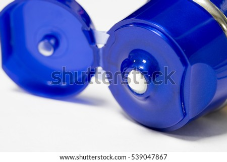 Opened cosmetic cream tube with blue cap on white background