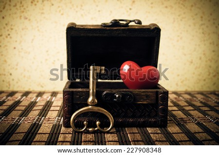 Opened decorative chest with heart and old metal key - stock photo