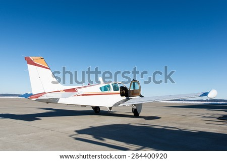 opened door of small propeller-driven aircraft at airstrip - stock photo