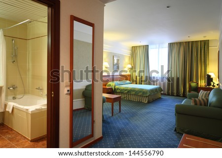 Opened door to bathroom and luxurious bedroom with green lilen. - stock photo
