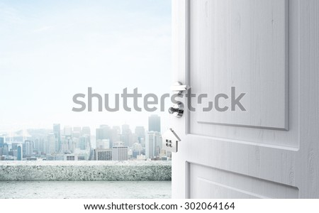 opened door with key in lock in city - stock photo