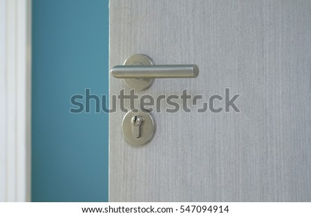 Opened door with metal door knob into blue room