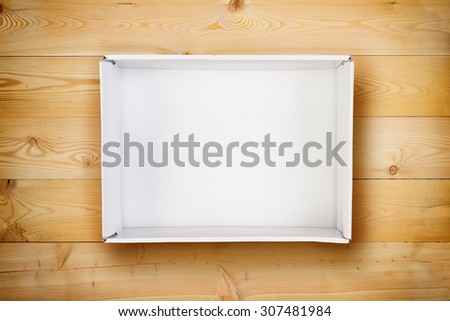 Opened empty cardboard box on wooden background. - stock photo