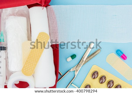 Opened first aid kit with medical equipment, on light blue background - stock photo