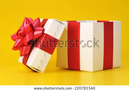 opened gift box close up isolated on yellow background  - stock photo